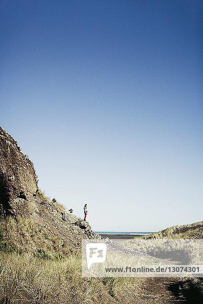Frau steht auf Fels am Strand vor klarem Himmel