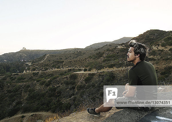 Full length of young man looking at view while sitting on rock against sky during sunset