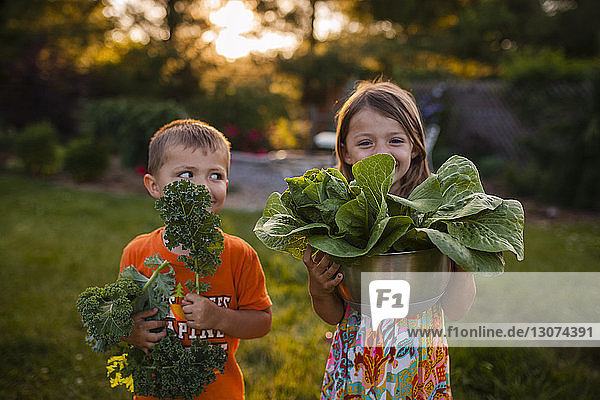Happy siblings carrying vegetables while standing in backyard