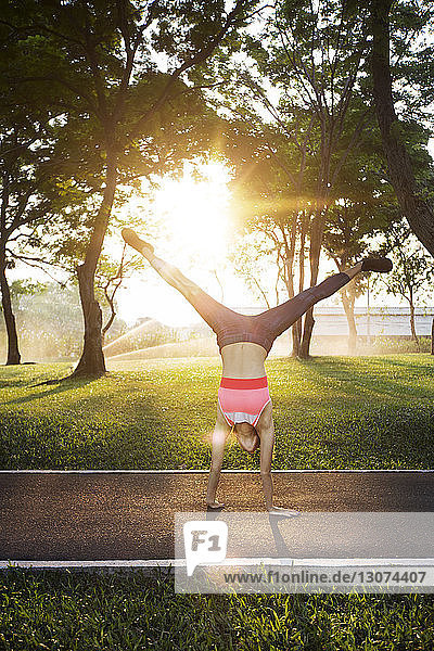 Woman performing handstand on road against trees in sunny day