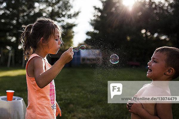 Boy looking at sister blowing bubble at backyard