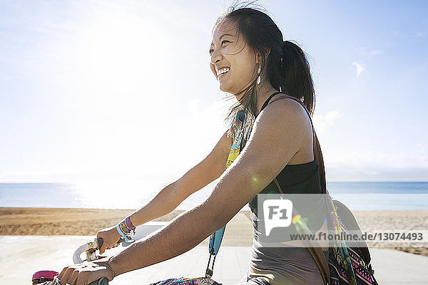 Side view of happy sporty woman riding bicycle by beach