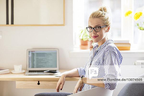 Porträt einer selbstbewussten Frau mit Laptop-Computer zu Hause