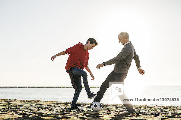 Full length of father and son playing soccer at beach against clear sky