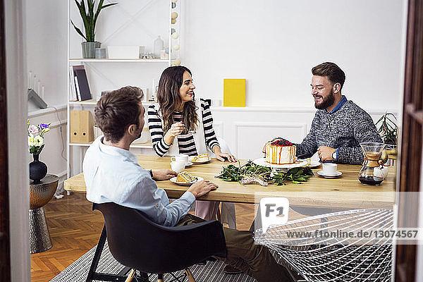 Glückliche Freunde essen Kuchen  während sie in einer Party am Esstisch sitzen