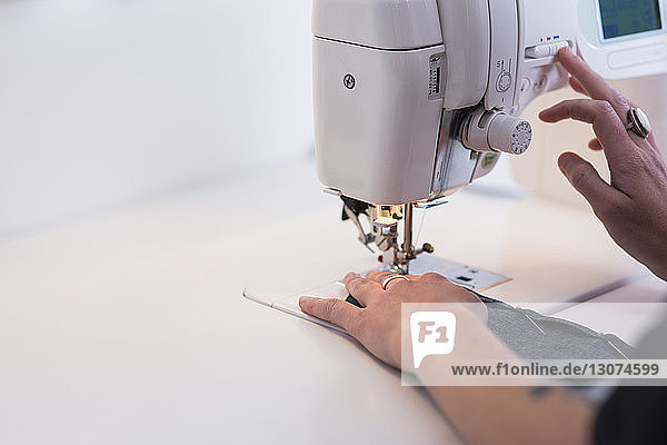 Cropped image of female tailor using sewing machine at table