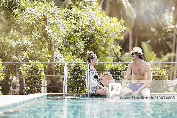 Happy couple relaxing at poolside
