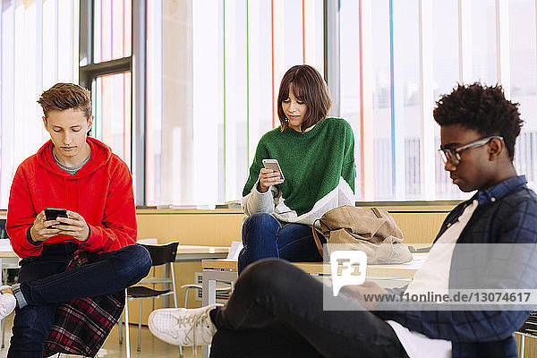 Students using mobile phones while sitting in library