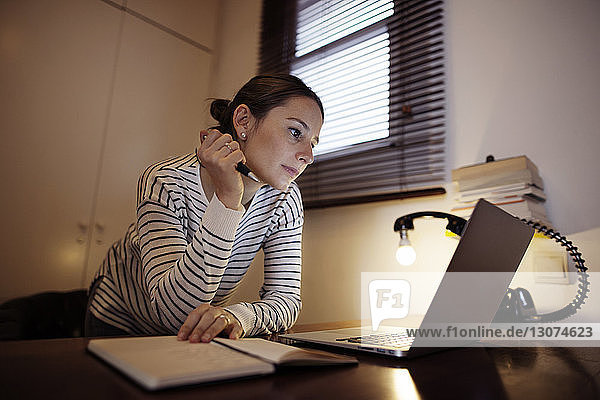 Woman working on laptop by desk lamp at table
