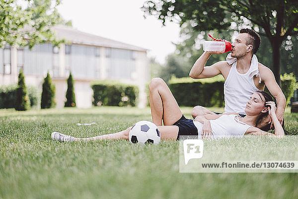 Junges Paar ruht sich auf dem Fussballfeld im Park aus