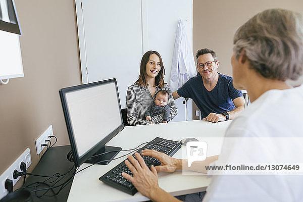 Glückliche Familie bespricht sich mit Arzt in medizinischer Klinik