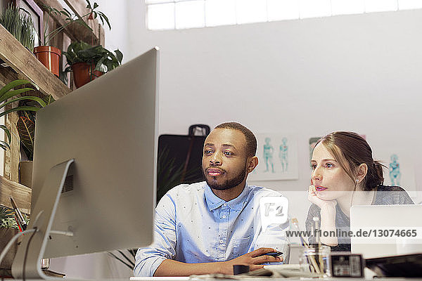 Multi-ethnic illustrators working on computer in creative office
