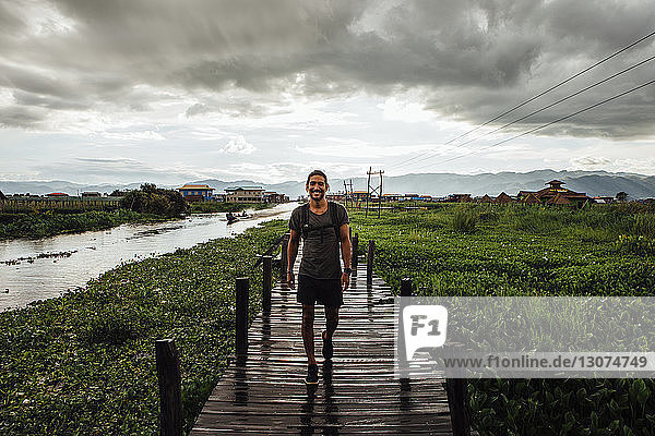 Portrait of man walking on footbridge by Inle lake against cloudy sky