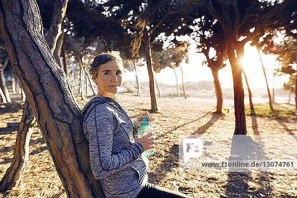 Portrait of female jogger leaning on tree while holding water bottle in park