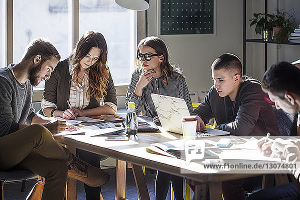 College students studying while sitting at table by window in classroom