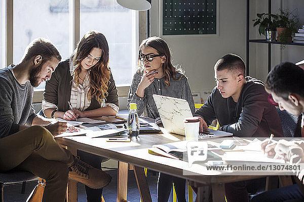 College-Studenten lernen  während sie im Klassenzimmer am Tisch am Fenster sitzen