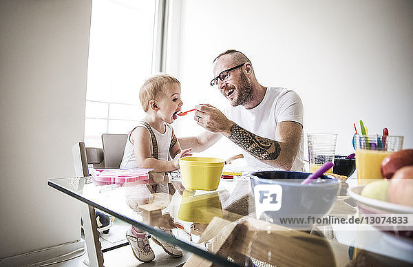 Happy father feeding daughter at breakfast table against brightly lit wall
