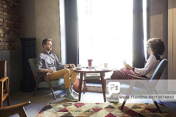 Geschäftskollegen diskutieren am Fenster in der Hotellobby