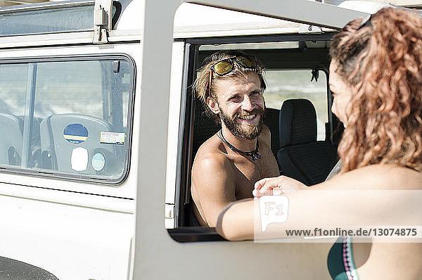Frau spricht mit einem Freund  der im Geländewagen am Strand sitzt