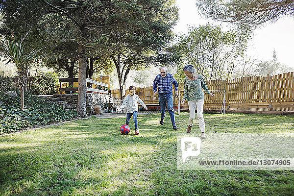 Großeltern spielen mit Enkel auf dem Hof Fußball