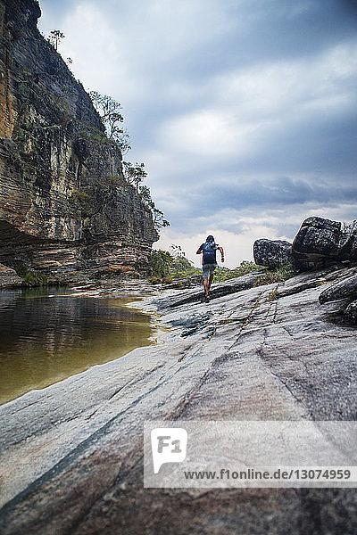 Rückansicht eines an einer Felsformation vor bewölktem Himmel vorbeilaufenden Menschen