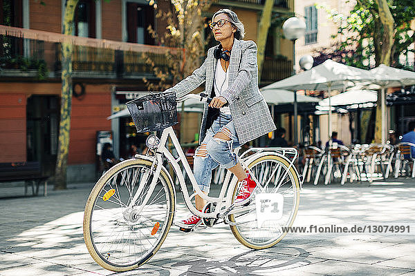 Full length of woman riding bicycle on street