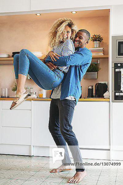 Full length of cheerful man carrying woman in kitchen at home