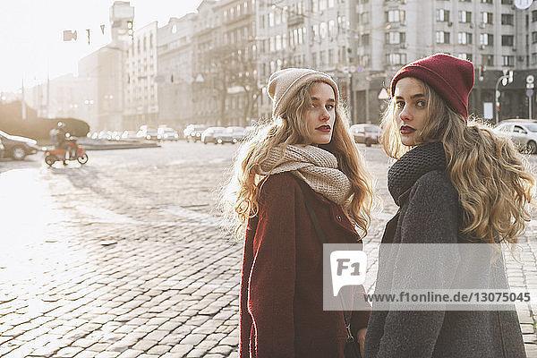 Porträt von Schwestern  die im Winter auf der Straße der Stadt stehen