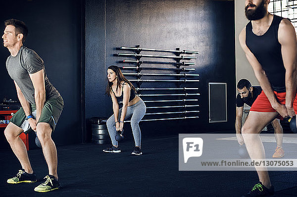 Athletes exercising with kettlebells in gym