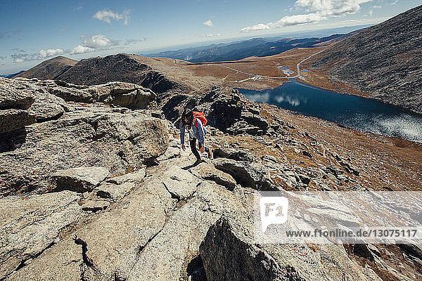 Wanderin besteigt Berg an sonnigem Tag