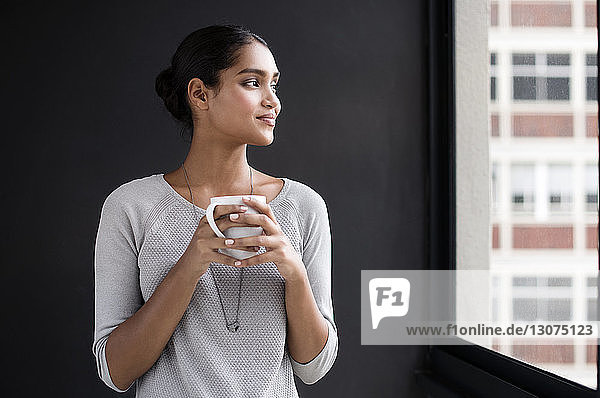 Smiling female interior designer holding coffee mug while looking through window in office