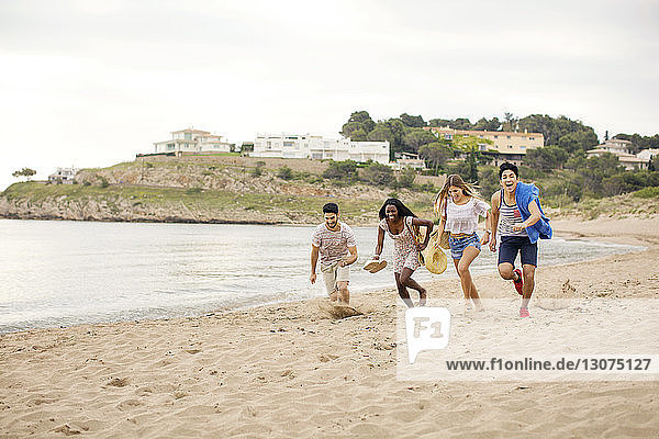 Playful friends running on shore at beach during vacation