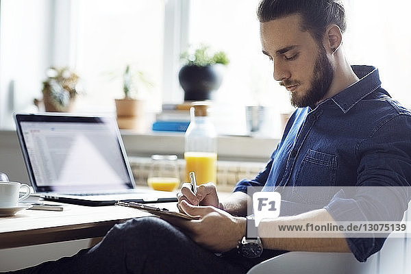 Man writing while sitting by table at home