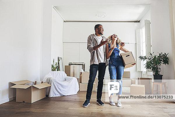 Lachendes Paar in voller Länge  während es in seinem neuen Zuhause steht