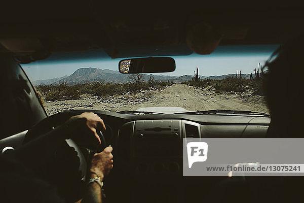 Ausgeschnittenes Bild von Freunden im Geländewagen auf unbefestigter Straße gegen Berge