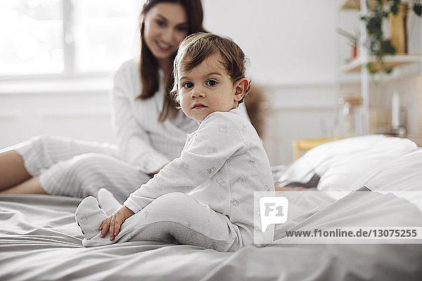 Porträt eines kleinen Jungen  der mit der Mutter zu Hause auf dem Bett sitzt