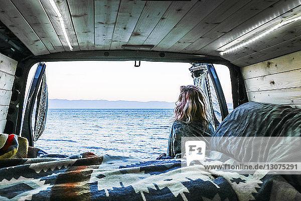 Rückansicht einer Frau  die aufs Meer schaut  während sie sich an einen Wohnwagen lehnt