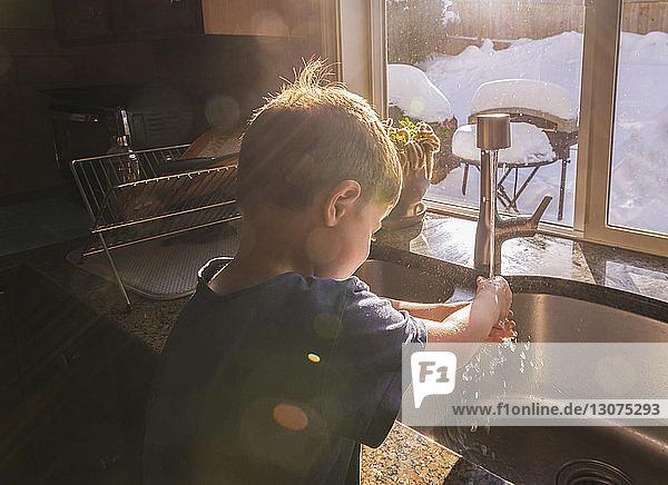 Junge wäscht sich im Winter die Hände am Küchenspülbecken am Fenster
