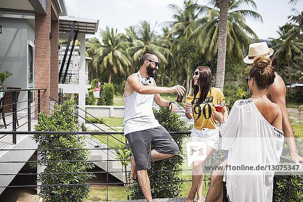 Fröhliche männliche und weibliche Freunde bei einem Drink am Touristenort