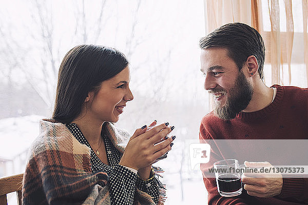 Smiling couple looking at each other while having drink in cafe