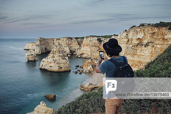 Wanderer fotografiert Berge auf dem Seeweg per Smartphone am Praia da Marinha