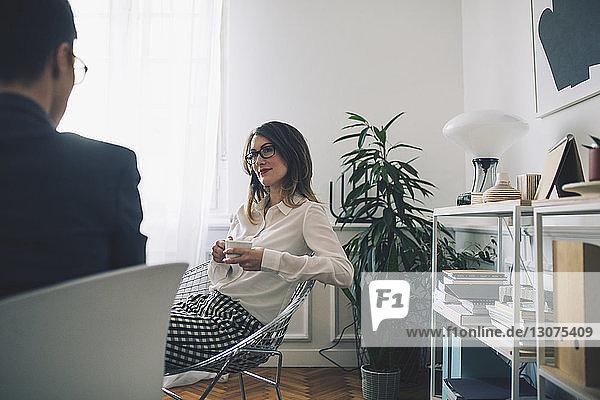 Geschäftsfrauen diskutieren bei einem Drink im Büro