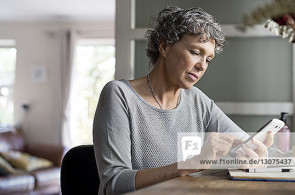 Mature woman using smart phone while working at home