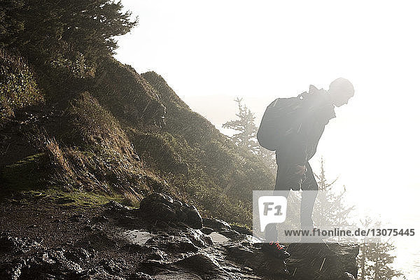 Side view of hiker with backpack standing on rocks against clear sky during rainfall