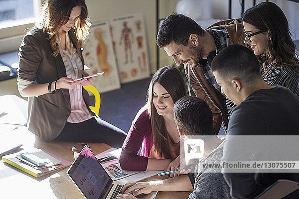 Hochwinkelansicht von Studenten  die während des Studiums im Klassenzimmer auf einen Laptop-Computer schauen
