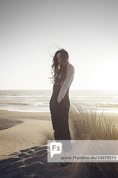 Woman with hands in pockets standing at beach against clear sky