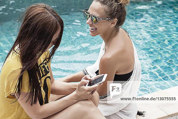 Hochwinkelansicht einer glücklichen Frau  die ein Smartphone benutzt  während sie sich mit einem Freund am Pool entspannt