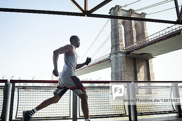 Side view of young man jogging by railing against Brooklyn Bridge