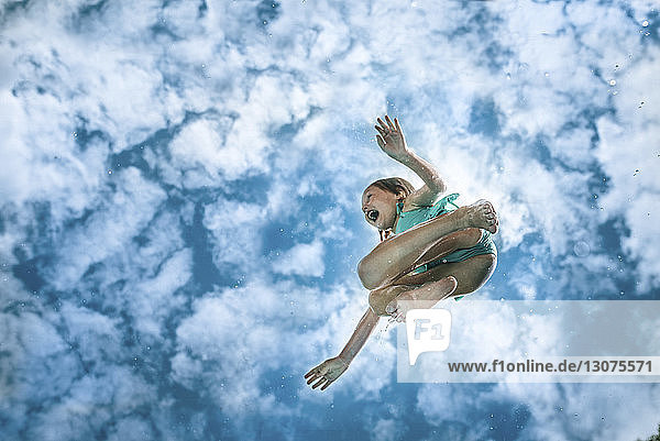Low angle view of carefree wet girl jumping against cloudy sky