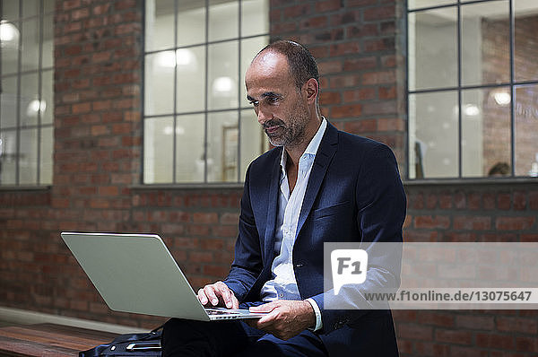 Businessman using laptop computer while sitting on seat against office